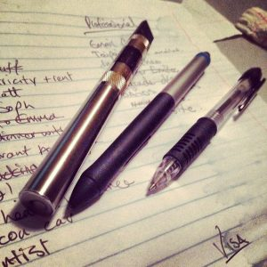Pens lay on a notebook page.
