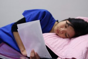 A woman in hospital scrubs reads notes while laying down.