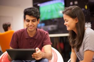 Two students look at an iPad.