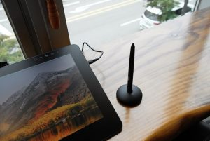 A stylus sits next to a tablet.