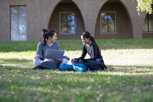 Two students sit on the grass.
