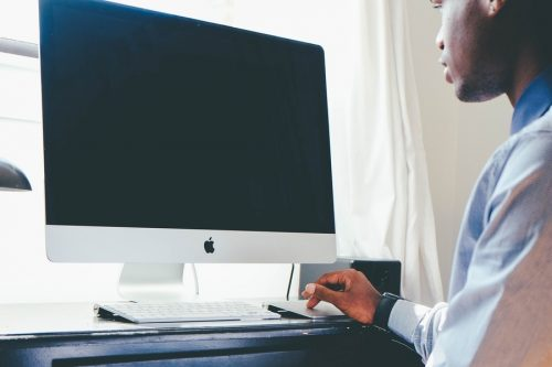 A man sits in front of a computer.