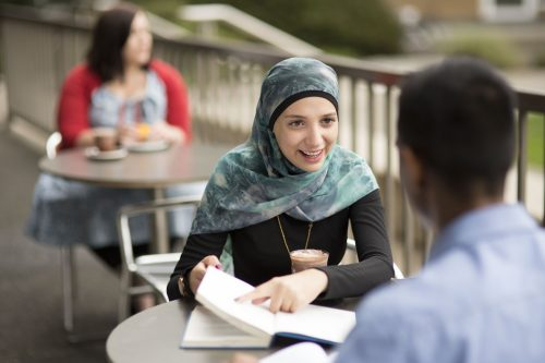 A young woman in a headscarf discusses with a colleague over coffee.
