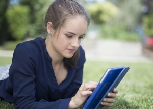 A young woman looks at an iPad.